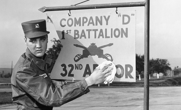 Elvis Presley, dressed in army fatigues, polishing a sign for company D in the 32nd armor division