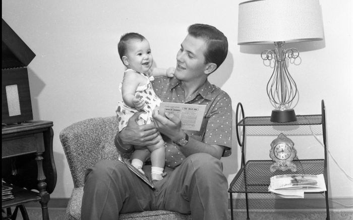 Pat Boone holding his baby daughter in a home setting